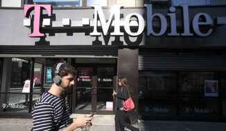 A man uses a cellphone as he passes a T-Mobile store in New York in this Sept. 12, 2012, file photo. (AP Photo/Mark Lennihan, File)