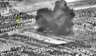 This image made from footage taken from Russian Defense Ministry official website on Friday, Oct. 2, 2015, shows another attack made from a fighter jet in Syria. The Russian Defense Ministry says its aircraft have carried out 18 sorties in Syria in the past 24 hours, including 10 overnight in which seven sites were bombed. The annotations on the image were made by the source and indicate the center of the target, and its direction, yellow. (AP Photo/ Russian Defense Ministry Press Service)