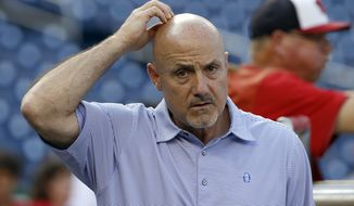 Washington Nationals general manager Mike Rizzo scratches his head before a baseball game against the New York Mets at Nationals Park, Tuesday, Sept. 8, 2015, in Washington. (AP Photo/Alex Brandon)