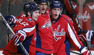 Washington Capitals center Evgeny Kuznetsov, left, from Russia, left wing Alex Ovechkin, from Russia, and defenseman Nate Schmidt celebrate Ovechkin's goal to tie the game in the third period of an NHL preseason hockey game against the Boston Bruins, Friday, Oct. 2, 2015, in Washington. The Capitals won 2-1 in a shootout. (AP Photo/Alex Brandon)