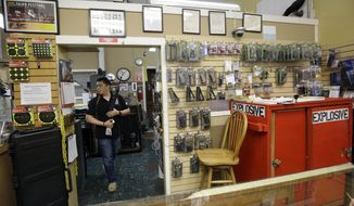 In this Wednesday, Sept. 30, 2015 photo, High Bridge Arms general manager Steve Alcairo holds a firearm while interviewed in San Francisco. High Bridge Arms, the last gun store in San Francisco, is scheduled to close on Oct. 31, 2015. (AP Photo/Jeff Chiu)