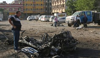 Civilians inspect the aftermath of a car bombing near a restaurant in a commercial area of central Baghdad, Iraq, Tuesday, Sept. 29, 2015. Iraqi officials say a car bomb exploded around midnight Monday in central Baghdad killing and wounding civilians. (AP Photo/Hadi Mizban) ** FILE **