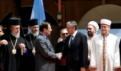 Cyprus' president Nicos Anastasiades and Turkish Cypriot leader Mustafa Akinci shake hands after a meeting at U.N. buffer zone at Ledra Palace Hotel in divided capital Nicosia, Cyprus in September. The heads of Cyprus' Christian and Muslim communities are meeting with the ethnically divided island's rival leaders to lend their support to ongoing reunification talks. (Associated Press)