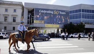 Police ride horses outside of the Community College of Philadelphia Tuesday, Oct. 6, 2015, in Philadelphia. Police have arrested a 17-year-old believed to have pulled a gun on a student outside the community college building, prompting a campus lockdown and a large police response. (AP Photo/Matt Rourke)