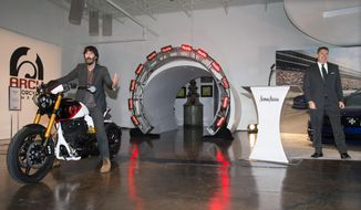 In this photo provided by Neiman Marcus, actor and Arch Motorcycles co-owner Keanu Reeves, left, is introduced by John Koryl, president of Neiman Marcus Stores and Online at Neiman Marcus, as he rides an Arch Motorcycle during the launch of the Neiman Marcus Christmas Book, Tuesday, Oct. 6, 2015 in Dallas. For $150,000, shoppers can buy a package for two that includes a limited edition KRGT-1 motorcycle and a two-day ride in the company of Reeves and Arch co-owner Gard Hollinger. (Tim Sharp/Neiman Marcus via AP)