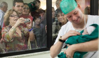 In this Aug. 2, 2012 photo, relatives watch as Romulo Coelho holds his newborn daughter, Hadassa, birthed via cesarean section at the Perinatal Clinic in Rio de Janeiro. In clinics like Perinatal, most new parents have medical insurance that cover the $4,200 price tag of the C-sections, plus a three-day stay in a private room. But that cost can rise considerably. (AP Photo/Felipe Dana, File)