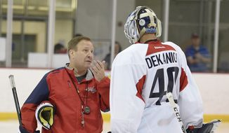 Washington Capitals goaltending coach Mitch Korn, left, talks with Mark Dekanich, right, during Media Day at NHL hockey training camp, Friday, Sept. 18, 2015, in Arlington, Va. (AP Photo/Nick Wass)