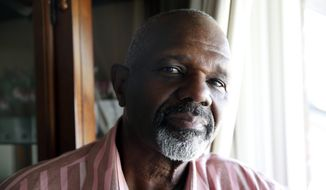 Kenneth Evans poses for a photograph in his home Wednesday, Sept. 16, 2015, in Temple Hills, Md. Drug criminals once described by prosecutors as unrepentant repeat offenders are among those poised to benefit from new sentencing guidelines that are shrinking punishments for thousands of federal prisoners, according to an Associated Press review of court records. Evans' son Tuan Evans is scheduled for early release from prison, the result of new sentencing guideline ranges that trim punishment lengths for convicted drug criminals. (AP Photo/Alex Brandon)