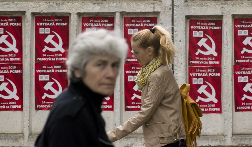 Pedestrians walk past election posters for the Communist Party in Chisinau, the capital city of Moldova. Repeated attempts to sell radioactive materials signal that a thriving nuclear black market has emerged in this impoverished corner of Eastern Europe on the fringes of the former Soviet Union. (AP Photo/Vadim Ghirda)
