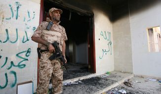 A Libyan military guard stands in front of one of the U.S. Consulate's burnt out buildings in Benghazi, Libya, on Sept. 14, 2012. (Associated Press)