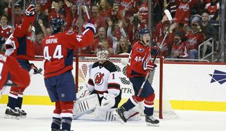 Washington Capitals defenseman Brooks Orpik (44) celebrates with center Michael Latta (46) after his goal past New Jersey Devils goalie Keith Kinkaid (1) during the first period of an NHL hockey game, Saturday, Oct. 10, 2015, in Washington. (AP Photo/Alex Brandon)