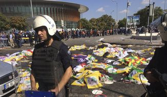 Bodies of victims are covered with flags and banners as a police officer secure the area after an explosion in Ankara, Turkey, Saturday, Oct. 10, 2015. Two bomb explosions apparently targeting a peace rally in Turkey's capital Ankara on Saturday has killed many people a news agency and witnesses said. (AP Photo/Burhan Ozbilici)