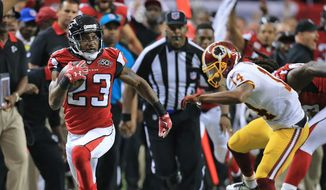 Atlanta Falcons cornerback Robert Alford intercepts Washington Redskins quarterback Kirk Cousins during overtime and returns the ball for the game winning touchdown in an NFL football game, Sunday, Oct. 11, 2015 in Atlanta. (Curtis Compton/Atlanta Journal-Constitution via AP)