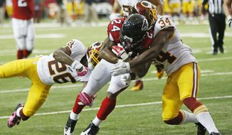 Atlanta Falcons running back Devonta Freeman (24) scores a touchdown as Washington Redskins strong safety Trenton Robinson (34) and Washington Redskins cornerback Bashaud Breeland (26) defend during the second half of an NFL football game, Sunday, Oct. 11, 2015, in Atlanta. (AP Photo/John Bazemore)