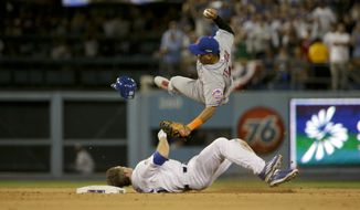 New York Mets shortstop Ruben Tejada goes over the top of the Los Angeles Dodgers' Chase Utley, who broke up a double play during the seventh inning in Game 2 of baseball's National League Division Series Saturday in Los Angeles. (Associated Press)
