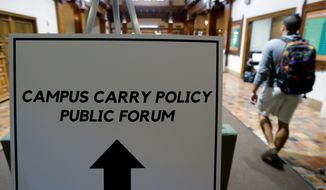 Students arrive a public forum on the University of Texas campus as a special committee studies how to implement a new law allowing students with concealed weapons permits to carry firearms into class and other campus buildings Sept. 30 in Austin, Texas. The law takes effect in August 2016. (Associated Press)
