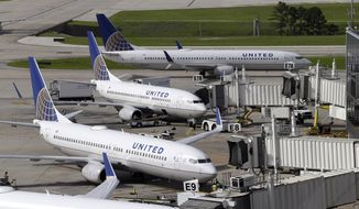 In this July 8, 2015, file photo, United Airlines planes are parked at their gates as another plane, top, taxis past them at George Bush Intercontinental Airport in Houston. U.S. airlines have ramped up an aggressive lobbying campaign that seeks nothing less than converting the government from industry regulator to business ally. (AP Photo/David J. Phillip, File)