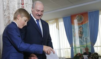 Belarusian President Alexander Lukashenko with his youngest son Nikolai casts his ballot at a polling station, during the presidential election, in Minsk, Belarus, Sunday, Oct. 11, 2015. (AP Photo/Sergei Grits)