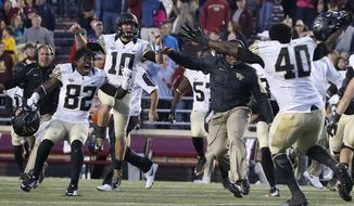 Wake Forest wide receiver P.J. Howard IV (82) and quarterback John Wolford (10) celebrate with teammates after time ran out on Boston College in the fourth quarter of an NCAA college football game in Boston, Saturday, Oct. 10, 2015. Wake Forest won 3-0. (AP Photo/Michael Dwyer)