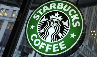 This Dec. 20, 2010 photo shows signage at a Starbucks store in New York's Times Square. (AP Photo/Richard Drew, File)