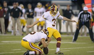 Washington Redskins kicker Dustin Hopkins (3) kicks an extra point as Tress Way holds during the second half an NFL football game against the New York Giants Thursday, Sept. 24, 2015, in East Rutherford, N.J. (AP Photo/Bill Kostroun)