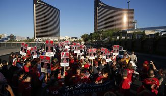 People chant during a rally in front of the Trump Hotel Monday, Oct. 12, 2015, in Las Vegas. Democratic presidential candidate Hillary Rodham Clinton spoke at the rally held by the Culinary Union to support a union drive at the Trump Hotel in Las Vegas. The hotel tower in back right belongs to the Wynn, where a Democratic presidential debate will be held Tuesday. (AP Photo/John Locher)