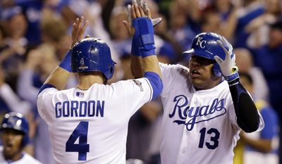 Kansas City Royals' Alex Gordon (4) and Salvador Perez (13) celebrate after scoring on a double by teammate Alex Rios during the fifth inning of Game 5 in baseball's American League Division Series against the Houston Astros, Wednesday, Oct. 14, 2015, in Kansas City, Mo. (AP Photo/Orlin Wagner)