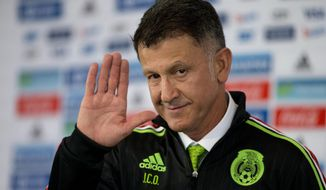 Juan Carlos Osorio, newly-appointed head coach of Mexico's national soccer team, waves after donning his team jacket during a press conference in Mexico City, Wednesday, Oct. 14, 2015. (AP Photo/Rebecca Blackwell)