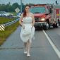 In this Oct. 3, 2015, photo provided by Marcy Martin Photography, her daughter Sarah Ray, in her wedding dress, attends to a car crash in Clarksville, Tenn. Ray's father and grandparents where in a car crash on their way to Ray's wedding reception. Ray, who is a paramedic, went to the scene to check on her relatives. (Marcy Martin Photography via AP)