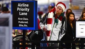 FILE - In this Dec. 24, 2014 file photo, Amos Darnell looks for a shorter line at the security checkpoint at Charlotte Douglas International Airport in Charlotte, N.C. Holiday travelers may find a little something extra in their stocking _ airfares should be a bit lower than last year. (Todd Sumlin/The Charlotte Observer via AP, File) MAGS OUT; TV OUT; MANDATORY CREDIT
