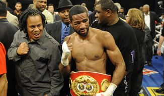 Lamont Peterson, center, poses after a boxing match against Amir Khan, of England, Sunday, Dec. 11, 2011, in Washington. (AP Photo/Nick Wass)