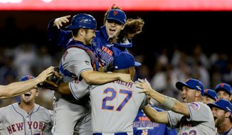 New York Mets starting pitcher Jacob deGrom, above right, catcher Travis d'Arnaud, left, and other Mets players celebrate a 3-2 win over the Los Angeles Dodgers in Game 5 of baseball's National League Division Series on Thursday, Oct. 15, 2015, in Los Angeles. (AP Photo/Alex Gallardo)