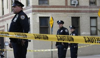 Police officers stand guard near an apartment building in the Bronx borough of New York, Thursday, Oct. 15, 2015. A 6-month-old girl died Thursday after being tossed from the window of an apartment building, witnesses and police said, the third child killed that way in the city in three months. (AP Photo/Mary Altaffer) ** FILE **