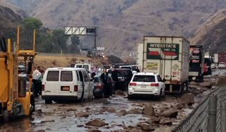 In this photo provided by Caltrans, vehicles are stopped in mud on California's Interstate 5 after flooding Thursday, Oct. 15, 2015. (Caltrans via AP)