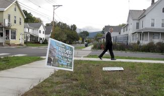 Rutland Police Cmdr. Scott Tucker walks at the corner of Library Avenue and Baxter Street in Rutland, Vt., in this Oct. 1, 2015, file photo. A decrepit building at the corner in the neighborhood was recently torn down so the lot could be turned into a park. (AP Photo/Wilson Ring)