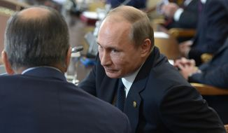 Russian President Vladimir Putin, right, talks with Russian Foreign Minister Sergey Lavrov, back to a camera, during a Commonwealth of Independent States, former Soviet republics, summit in Astana, Kazakhstan, Friday, Oct. 16, 2015. Putin on Friday warned leaders of Central Asian nations of a possible militant incursion from Afghanistan. (Alexei Nikolsky, RIA-Novosti, Kremlin Pool Photo via AP)