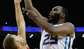 Al Jefferson of Charlotte Hornets, right, tries to shoot over Blake Griffin of Los Angeles Clippers during the NBA Global Games at the Mercedes-Benz Arena in Shanghai, China, Wednesday, Oct. 14, 2015. (AP Photo/Andy Wong)