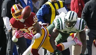 Washington Redskins cornerback Bashaud Breeland, left, makes an interception on a pass intended for New York Jets wide receiver Brandon Marshall during the first half of an NFL football game, Sunday, Oct. 18, 2015, in East Rutherford, N.J. (AP Photo/Gary Hershorn)