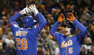 New York Mets' Daniel Murphy is congratulated by teammate David Wright after hitting a two-run home run during the first inning of Game 2 of the National League baseball championship series against the Chicago Cubs on Sunday, Oct. 18, 2015, in New York. (AP Photo/David J. Phillip)