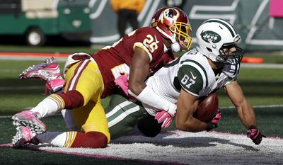 New York Jets wide receiver Eric Decker, right, scores on a touchdown pass from quarterback Ryan Fitzpatrick, not pictured, as Washington Redskins cornerback Bashaud Breeland makes the hit during the second half of an NFL football game, Sunday, Oct. 18, 2015, in East Rutherford, N.J. (AP Photo/Seth Wenig)