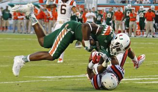 Miami tight end David Njoku (86) holds on for a long pass reception as he is brought down by Virginia Tech defender Wright Bynum (36) in the second half of an NCAA college football game, Saturday, Oct. 17, 2015, in Miami Gardens, Fla. Miami won the game 30-20. (AP Photo/Joe Skipper)