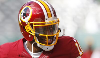Washington Redskins quarterback Robert Griffin III warms up prior to an NFL football game against the New York Jets, Sunday, Oct. 18, 2015, in East Rutherford, N.J. (AP Photo/Gary Hershorn)