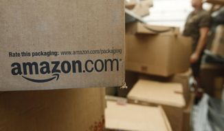 In this Oct. 18, 2010 file photo, an Amazon.com package awaits delivery from UPS in Palo Alto, Calif. Amazon is suing more than 1,000 people for advertising their services writing fake reviews for as little as $5 as it seeks to crack down on bogus reviews on its site. The complaint filed Friday, Oct. 16, 2015, in King County Superior Court in Seattle marks the latest effort by the online powerhouse to crack down on fraud on its site. (AP Photo/Paul Sakuma, File)