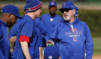 Chicago Cubs manager Joe Maddon, right, talks to Chris Coghlan during a team workout in preparation for Tuesday's Game 3 in baseball's National League Championship Series against the New York Mets, Monday, Oct. 19, 2015, in Chicago. (AP Photo/Charles Rex Arbogast)