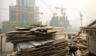 A worker tosses boards onto the back of a truck at a construction site in Beijing, in this Oct. 6, 2015, file photo. China's economic growth decelerated in the latest quarter but relatively robust spending by Chinese consumers helped to avert a deeper downturn. The world's second-largest economy grew by 6.9 percent in the three months ended in September, the slowest since early 2009 in the aftermath of the global crisis, data showed Monday, Oct. 19, 2015. That was down from the previous quarter's 7 percent. (AP Photo/Mark Schiefelbein, File)