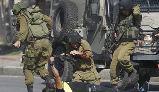 An Israeli soldier runs to help another who was just stabbed by a Palestinian, seen on the ground holding a knife, during clashes in Hebron, West Bank, in this Oct. 16, 2015, file photo. The clashes between Israelis and Palestinians in the Holy Land are not just physical; the two sides cannot agree on what they see, how they got here, who is to blame or where they should go. (AP Photo/Nasser Shiyoukhi, File)