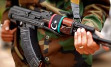 With a Libyan flag on his automatic weapon, a soldier stands guard outside a meeting between Secretary of State Hillary Rodham Clinton and Libya's Transitional National Council President Mustafa Abdel-Jalil at the World Islamic Call Society Headquarters in Tripoli, Libya, on Oct. 18, 2011. (Associated Press)