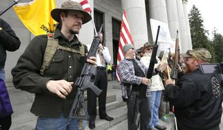 Gun owners display their weapons during a gun-rights rally on Jan. 15, 2015, at the Capitol in Olympia, Wash. The protesters were demonstrating against the state's Initiative 594, which requires - with only a few exceptions - background checks on all gun sales and transfers. (Associated Press)