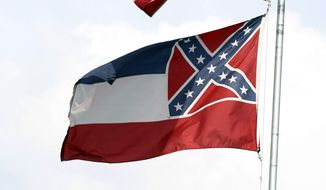 The American and Mississippi state flags fly on a flag pole outside the City Hall in McComb, Miss. (Associated Press)