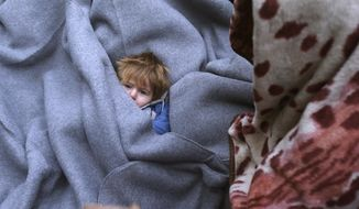 A migrant child is muffled up in blankets while resting on the road near a borderline between Serbia and Croatia, near the village of Berkasovo, Serbia, Tuesday, Oct. 20, 2015. (AP Photo/Darko Vojinovic)